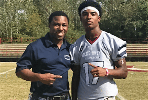With multiple scholarship offers in place, Terence Dunlap (right) was recently recognized by NFL trainer Reggie Young (left) during the nationwide Blue-Grey Jersey Presentation Tour.
